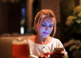 Pretty blonde woman looking at smartphone in cafe