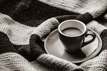 a cup of coffee and winter scarf. Image in white and black color style