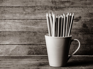 pencils in cup on a wooden background. Image in black and white style