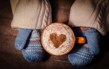 hands in mittens holding a cup of coffee with a heart symbol of cinnamon and cream