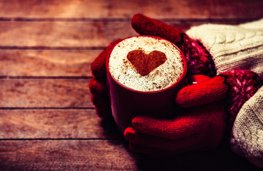 Hands in mittens holding hot cup of coffee. Photo with focus on heart.