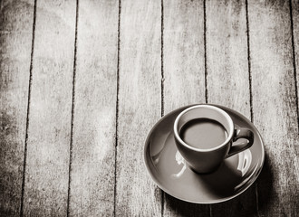 Little a cup of coffee on a wooden table. Image in white and black color style