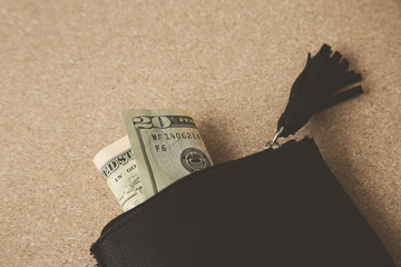 A man taking twenty USA dollars from a black leather purse. This image can be used to represent prudence with money or budgeting.