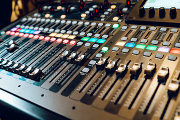 Professional audio mixing console with faders and adjusting knobs,TV equipment. The DJ is adjusting the volume of the sound.