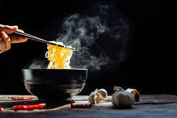 Hand uses chopsticks to pickup tasty noodles with steam and smoke in bowl on wooden background, selective focus. Asian meal on a table, junk food concept