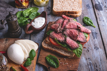 Wall Mural - Steak sandwich, sliced roast beef, cheese,spinach leaves,tomato. Rustic,on a wooden surface