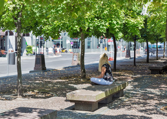 Young woman sitting on bench in city park. Fototapete