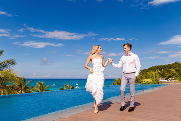 Beautiful blonde bride in white wedding dress and the groom dance in a hotel near the infinity pool. Tropical sea, sky and palm trees in the background. Summer vacation concept.