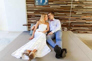Beautiful blonde bride in white wedding dress and the groom in the hotel.