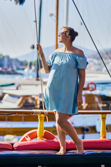Luxury travel on the yacht. Young woman enjoying sunset on boat deck sailing the sea.