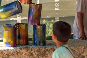 Little children throw balls on cans on a stall party. Concept: Speil and fun
