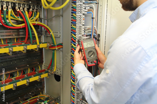 electrician is working in electrical cables distribution fuse box electrician is working in electrical cables distribution fuse box multimeter