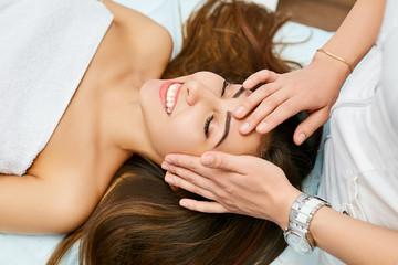Lovely girl on facial rejuvenation procedure. Massage in the beauty salon