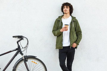Stylish man with curly hair, holds disposable cup of coffee, dressed in stylish clothes, models against white concrete wall, has break after riding bike, concentrated into distance. People and style