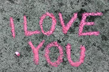 Colorful chalk drawing on asphalt: Pink words I LOVE YOU