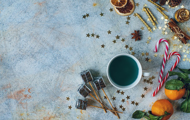New Year or Christmas composition with blue tea, tangerines, dry oranges, cones, cinnamon, gifts,candles, candies and toys on light rustic table. Seasonal home decoration,  top view, copy space