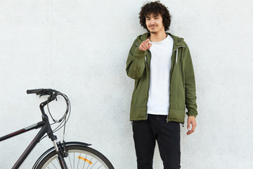 Photo of self confident male has curly hair, dressed in fashionable anorak, points with index finger directly at camera, makes choice, asks you to ride bicycle together with him, isolated on white