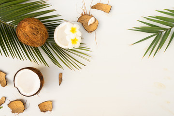 Summer flat lay scene with palm leaves and frangipani flowers with coconuts on wooden background with copy space