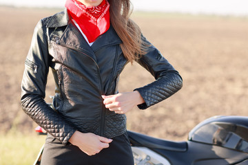 Cropped image of woman zips leather black jacket, wears red bandana on neck, prepares for motorrbike race, stands near bike outdoor against blurred background. People and street style concept