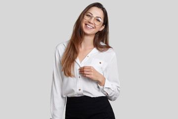 Smiling young lady has toothy smile, pleasant appearance, wears round spectacles, dressed in formal clothes, isolated over white background. Woman office worker rejoices success in her career