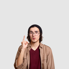 Photo of surprised guy has idea, raises fore finger, wears casual clothes, black hat, beige shirt round spectacles, indicates upwards, free space for your information above head. Indoor shot.