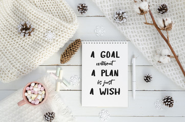 New year motivation a goal without a plan is just a wish. Christmas decorations, knitted blanket, pine cones,cotton flower, marshmello on wooden white background. Flat lay, top view, quote