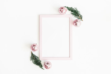 Christmas composition. Photo frame, pink decorations, fir tree branches on white background. Christmas, winter, new year concept. Flat lay, top view, copy space