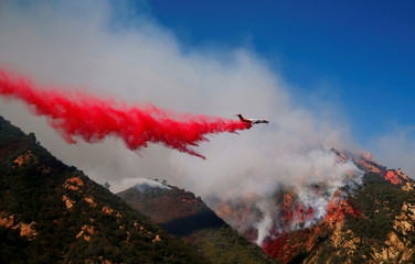 An aircraft drops flame retardant as firefighters battle the Woolsey Fire as it continues to burn in Malibu