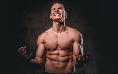 Portrait of an angry young man with a muscular body on dark background.