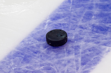 Puck on ice hockey rink surface, sport background