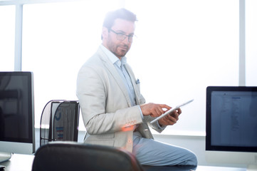 attentive businessman uses a digital tablet in a modern office.