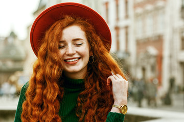 Close up portrait of young beautiful fashionable happy smiling redhead woman with freckles, very long curly hair, wearing green turtleneck, orange hat, golden wrist watch, posing in street. Copy space