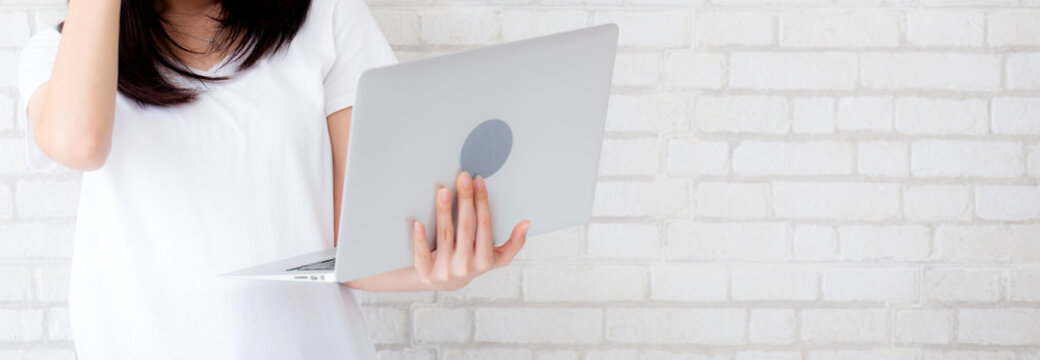 Banner website asian woman standing holding laptop on brick cement wall background, girl working computer, business and lifestyle concept.