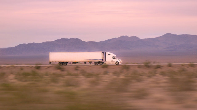 CLOSE UP: Freight semi truck driving and transporting goods on empty highway