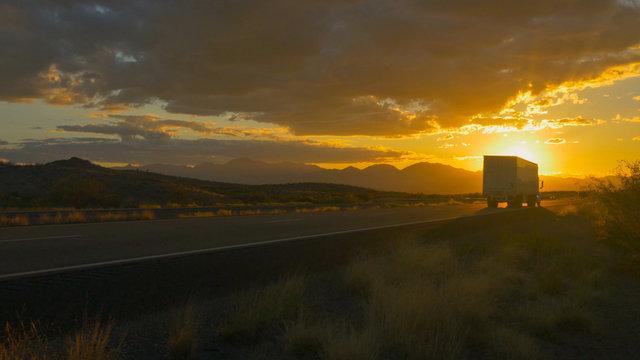 Freight semi truck speeding on empty highway over golden sun at summer sunset