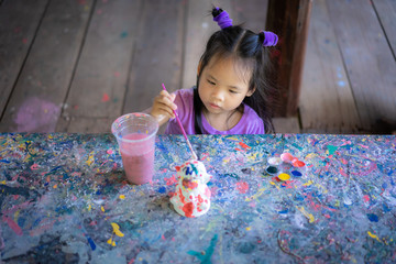 Asian cute little girl having fun to paint on stucco doll