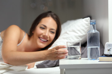 Happy girl catching a glass of water on the bed in the night