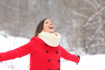 Joyful woman breathing fresh air enjoying snow