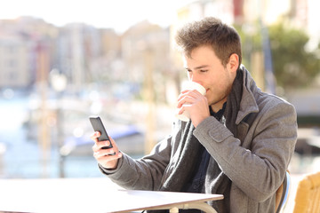 Man drinking and cheking smart phone content