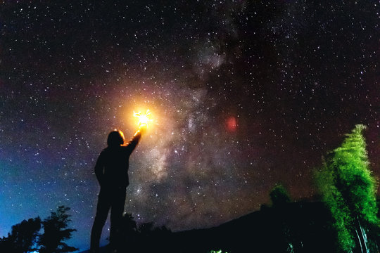 Silhouette of a standing human looking milky way at the night time. Light holds up over his head.
