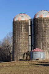 Composition of two large and one small silo in a winter landscape, vertical aspect