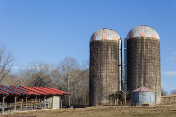Exterior of old grain silos by modern animal stalls with solar panels, winter, horizontal aspect