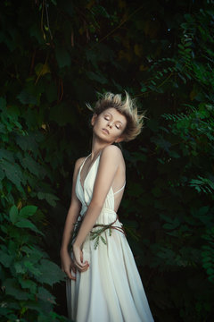 Young model is posing as a fairy in a forest