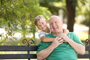 Elderly man with grandson on bench in park
