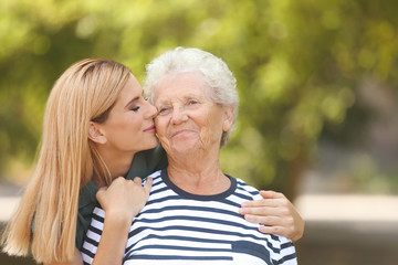 Woman with elderly mother outdoors on sunny day