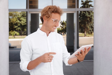 Male real estate agent with tablet outdoors