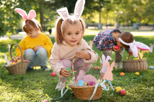 Cute little children hunting eggs in park. Easter tradition