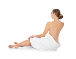 Young woman with soft towel sitting on white background