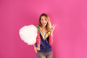 Young pretty woman with cotton candy on colorful background