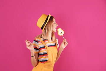 Young pretty woman with candy on colorful background Fototapete